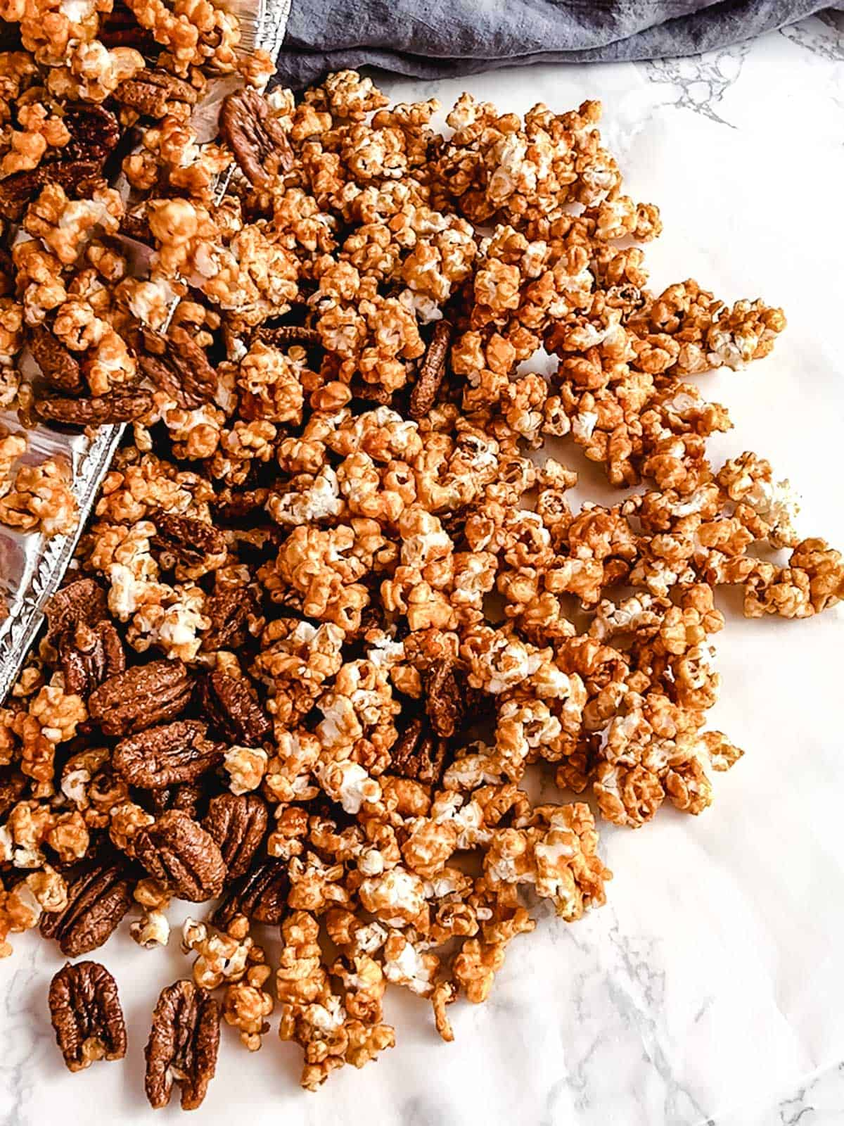 Pouring the Bourbon Pecan Praline Popcorn onto parchment paper for it to cool.
