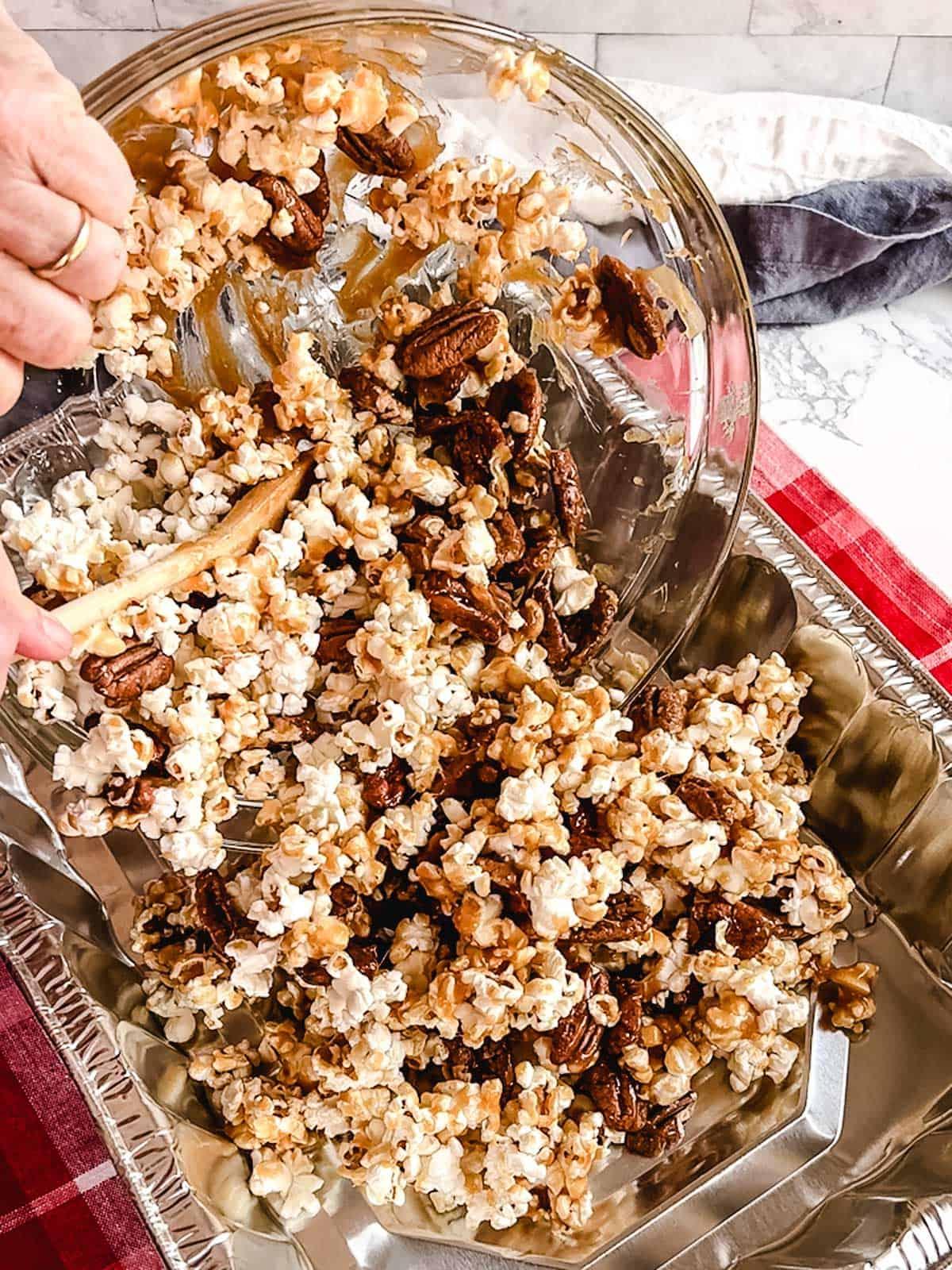 Dumping the pecan praline popcorn into a large aluminum roasting pan.